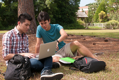 two students sitting on the grass in a park, both are looking at a laptop