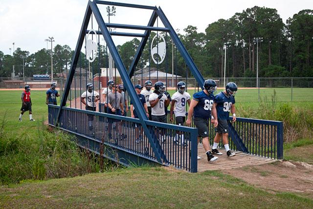 football team walking over eagle creek