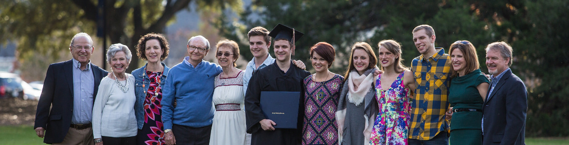 family group poses with a newly minted graduate
