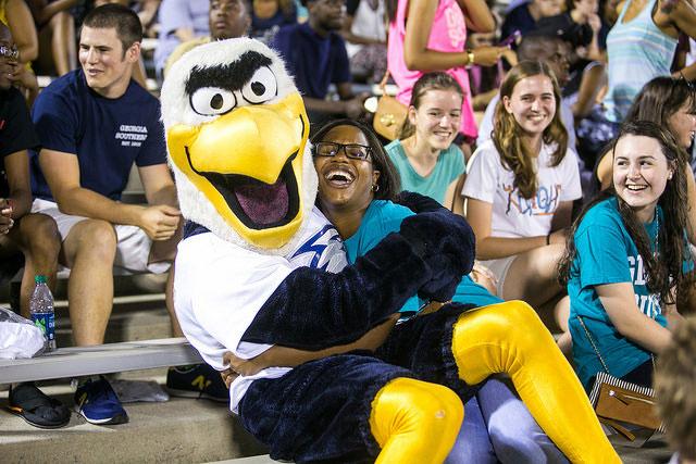 gus mascot hugging fan at football game