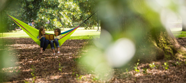 two female students share a hammock in a shady spot