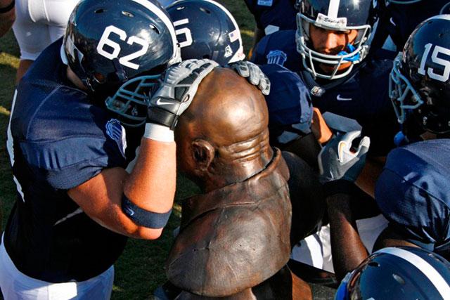 football team surrounding Erk Russel's statue