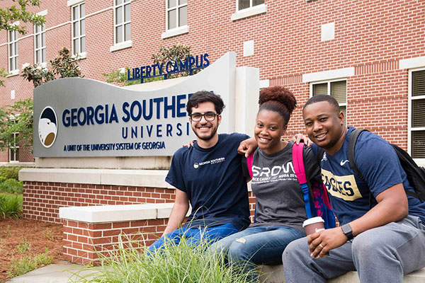 three students sitting in front of the liberty campus Georgia Southern sign