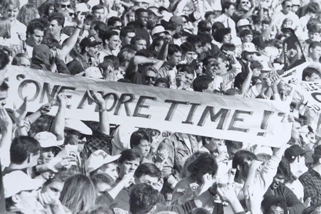 historic photo of fans in stands holding a sign saying One More Time