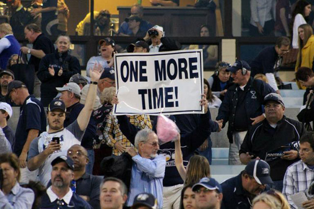 fans in stands holding sign saying One More Time