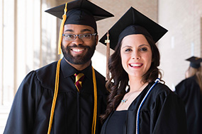 two students in graduation robes