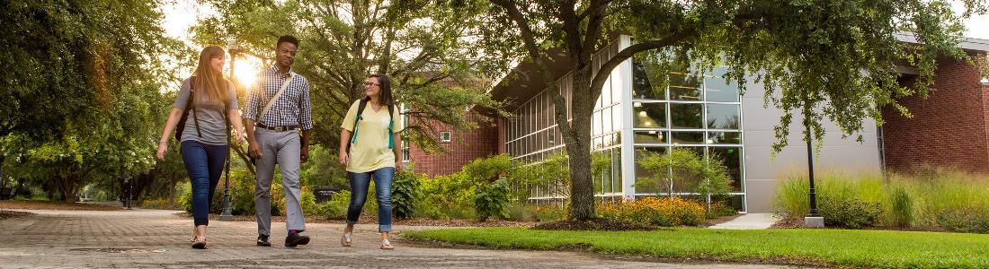 students walking on an expansive pedestrian way pass a modern building