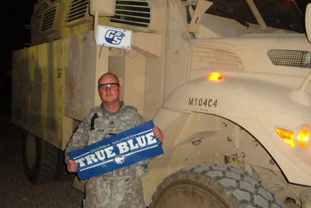 military man standing in front of a large military vehicle holding a true blue sign