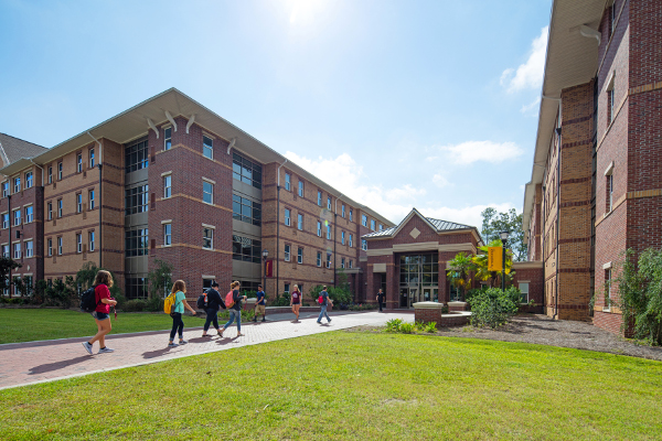 people walking into a modern four-story residence hall that looks a bit like a hotel