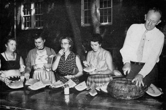 historic photo of people eating watermelon